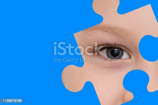 istock Kid spies through a blue puzzle. Symbol of autism awareness 1139978795