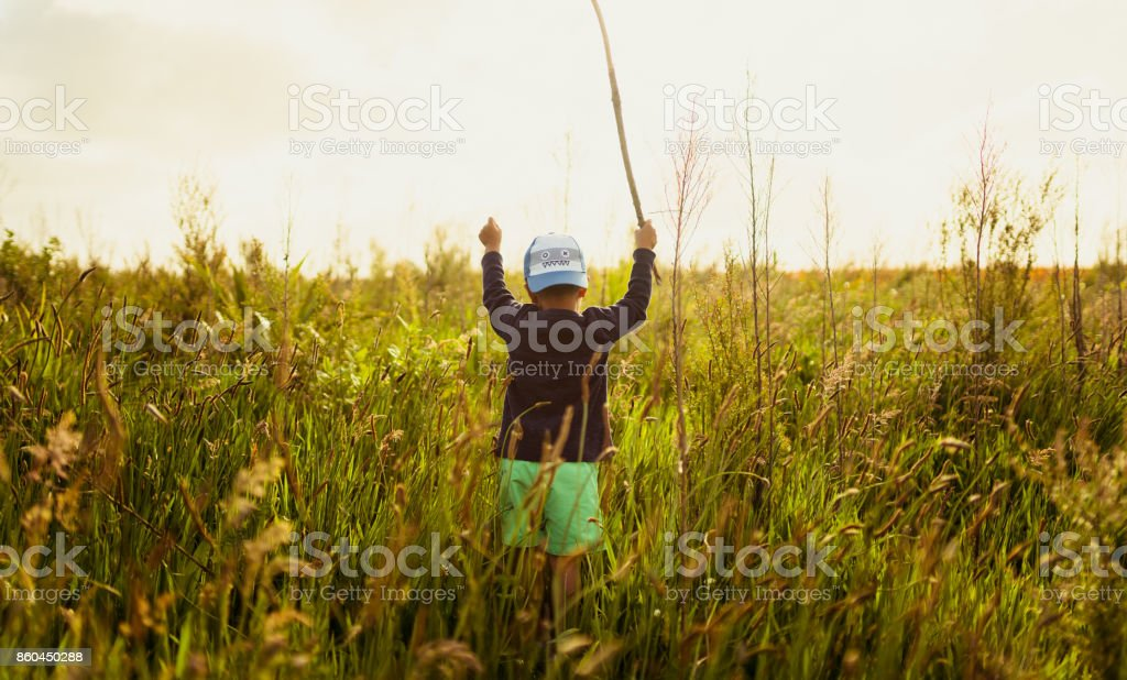 Kid standing in middle of grassy field with stick in his hand. stock photo