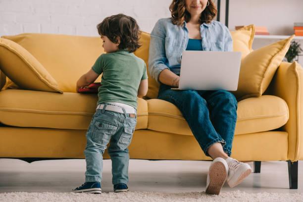 Kind steht in der Nähe von Sofa, während Mutter mit Laptop – Foto