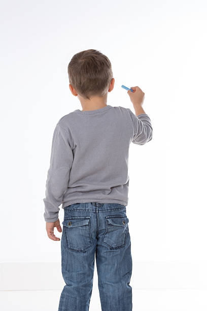 kid thinking with chalk in hand stock photo