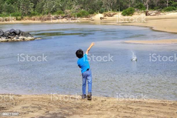 Barn Som Kastar Sten I Vatten-foton och fler bilder på Aktivitet