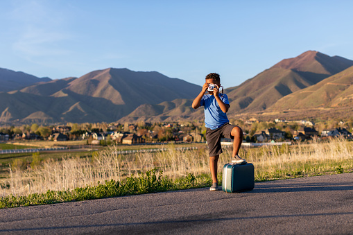 A young boy dreams of the day he can take his bags, camera, and dreams to the road. He loves to travel. Image taken in Utah, USA.