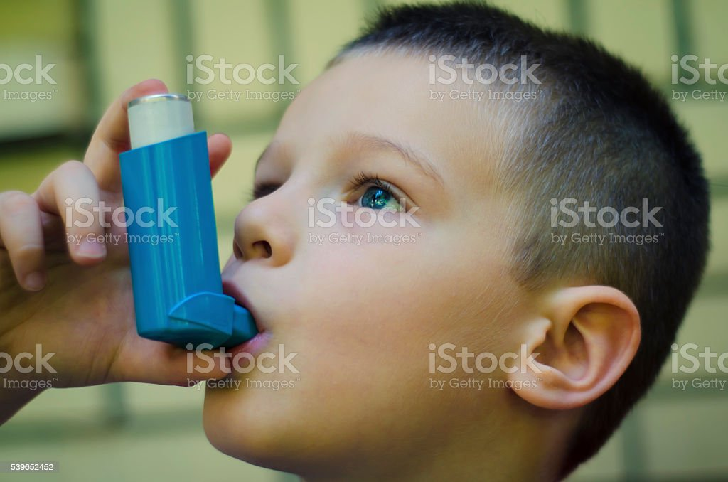 Kid using inhaler stock photo