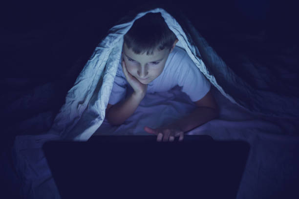 Kid using laptop in dark room stock photo