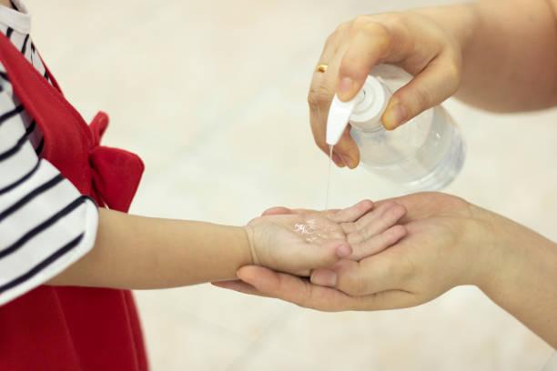 子供の使用衛生剤アルコールゲルクリーン手保護感染ウイルスクレンザー - 衛生 ストックフォトと画像