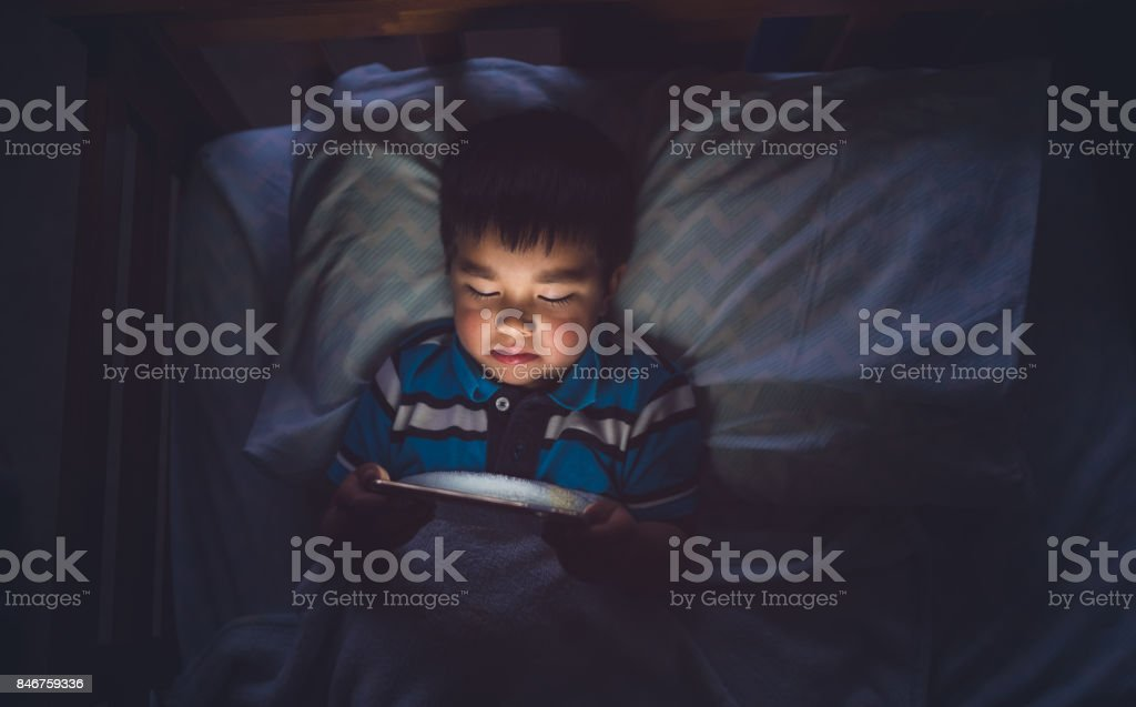 Kid Using Smartphone On Bed. stock photo