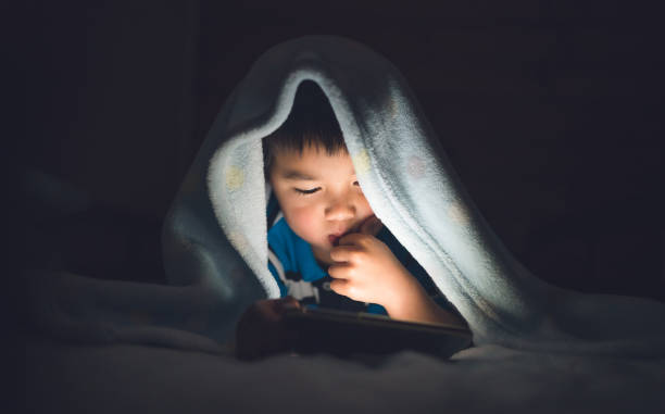 kid using smartphone on bed. - smartphone addiction not groups stock pictures, royalty-free photos & images