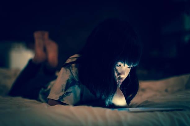 Kid using tablet in darkness bedroom. stock photo