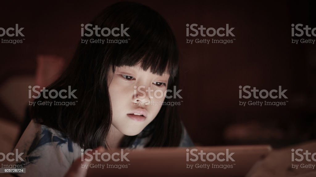 Kid using tablet with light reflex on face. stock photo