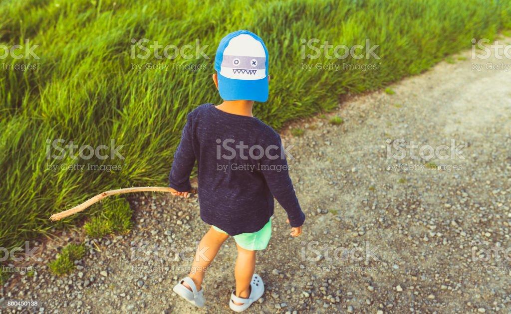 Kid walking by grassy pasture. stock photo