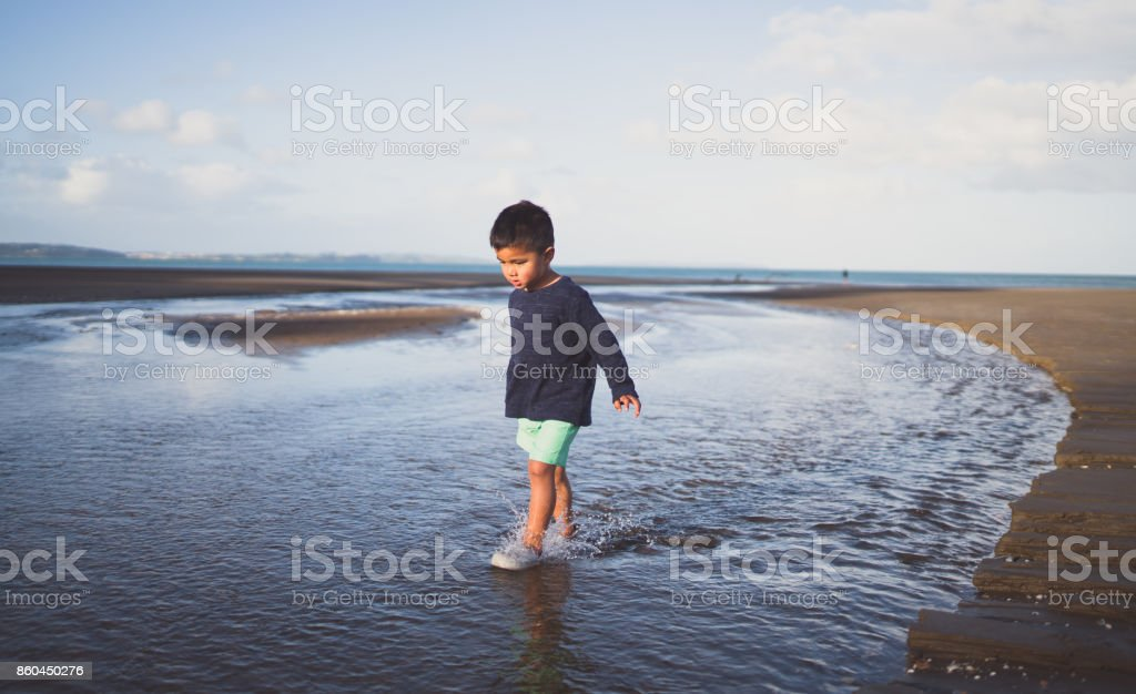Kid walking in water at long bay, Auckland, New Zealand. stock photo
