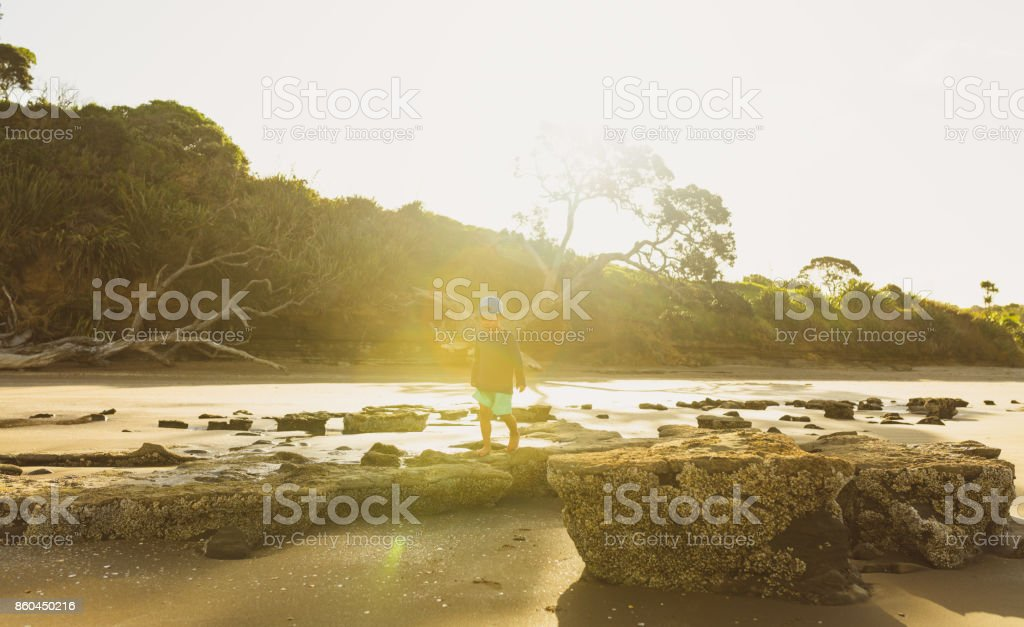 Kid walking on rocks at beach with sunset in background, Auckland, New Zealand. stock photo