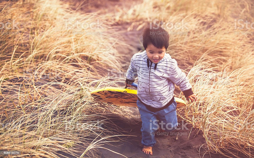 Kid Walking With Sand Board. stock photo