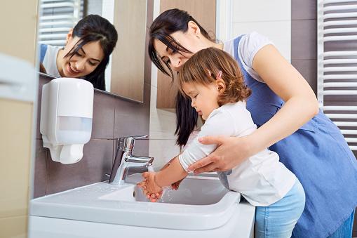 Lavarse Las Manos De Niños Con Mamá En El Baño Foto de stock y más banco de imágenes de Adulto