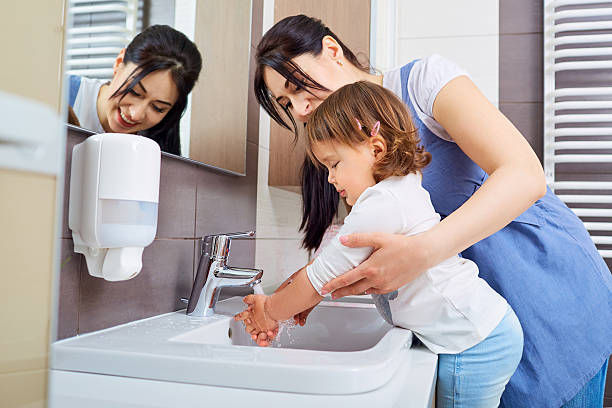 kid washing hands with mom in the bathroom. - washing hands bildbanksfoton och bilder