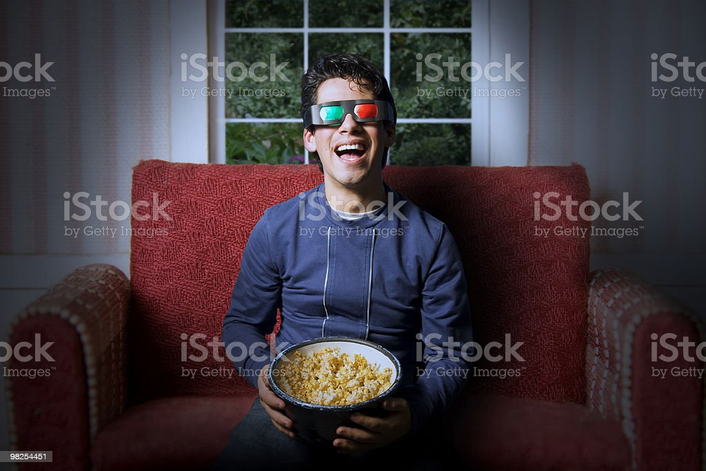A kid wearing 3D glasses with a bowl of popcorn on a chair royalty-free stock photo