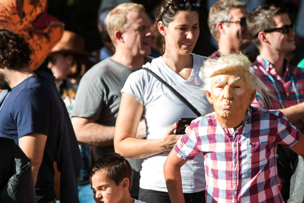 kid wears donald trump mask at popular atlanta halloween parade - trump стоковые фото и изображения