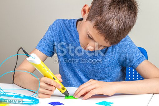 899701486 istock photo Kid with 3d printing pen creating new item 1182932813