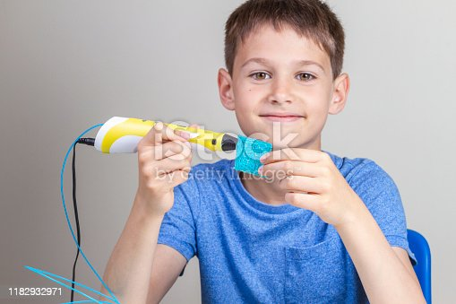 899701486 istock photo Kid with 3d printing pen creating new item 1182932971
