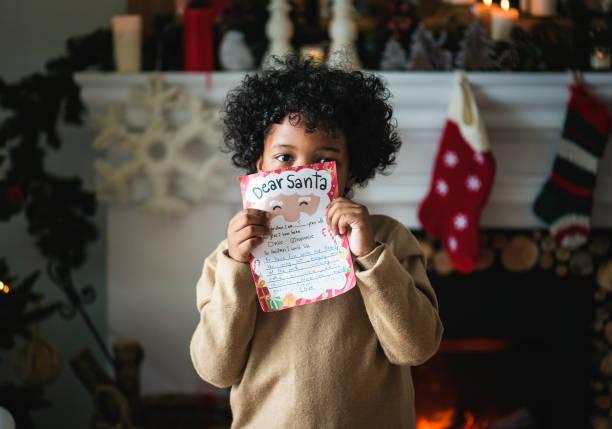 kind mit weihnachts-wunschliste - weihnachts wunschliste stock-fotos und bilder