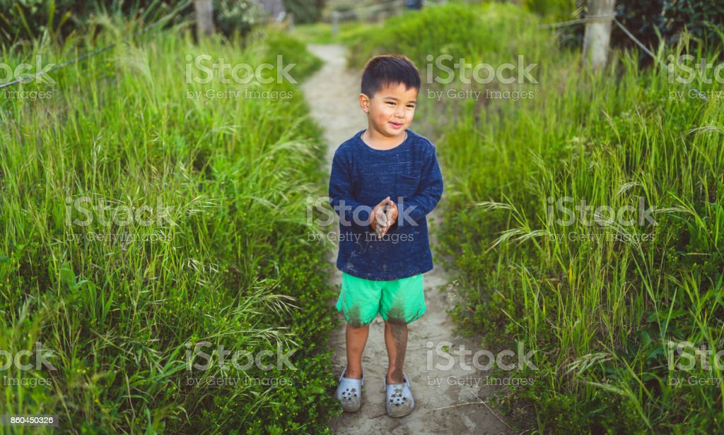 Kid with dirty hands and clothes. stock photo