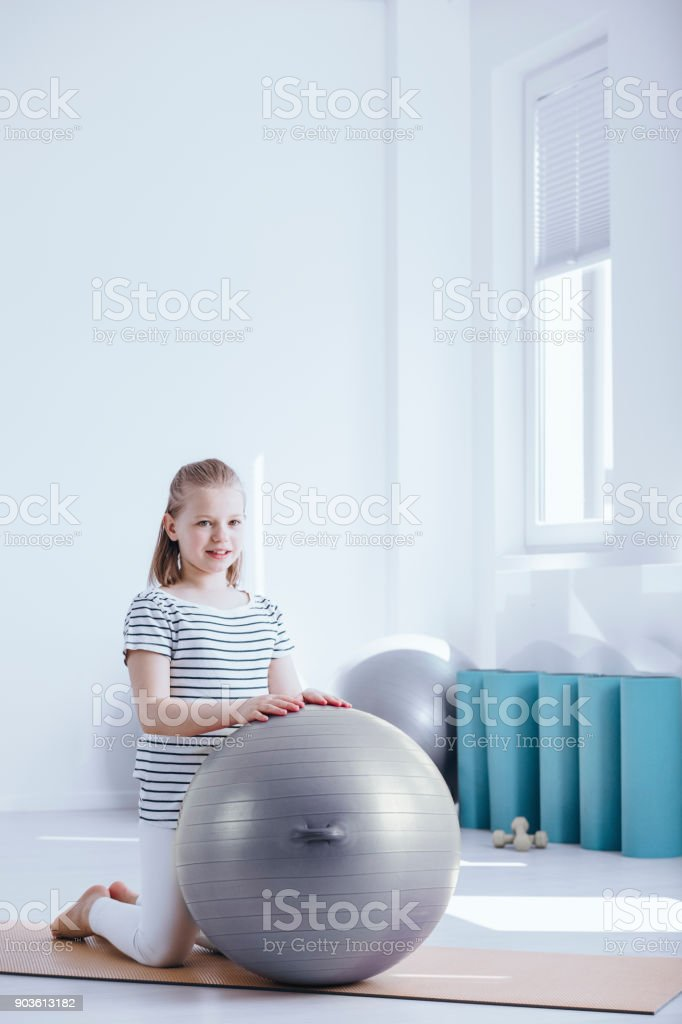 Young kid waiting for her physiotherapist with grey exercise ball at...