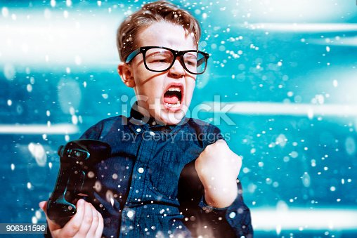 istock Kid with game controller wins sport match and cheers 906341596