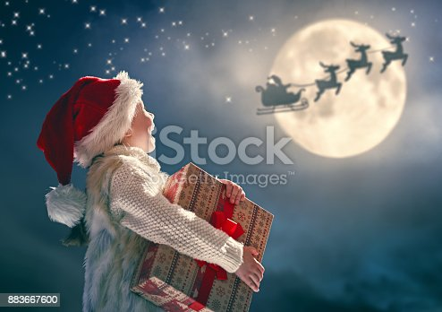 istock kid with gift on dark background 883667600