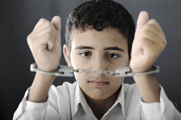 kid with handcuffs on hands - boy handcuffs stock pictures, royalty-free photos & images