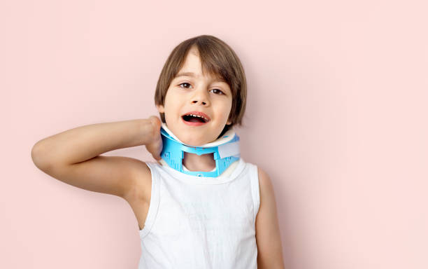 Kid with neckache wearing a cervical collar brace stock photo