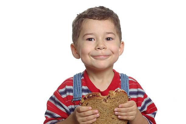 Kid With Peanut Butter and Jelly Sandwich A five-year-old boy holds a whole-wheat peanut butter and jelly sandwich with a bite taken out of it, isolated on white background bib overalls boy stock pictures, royalty-free photos & images