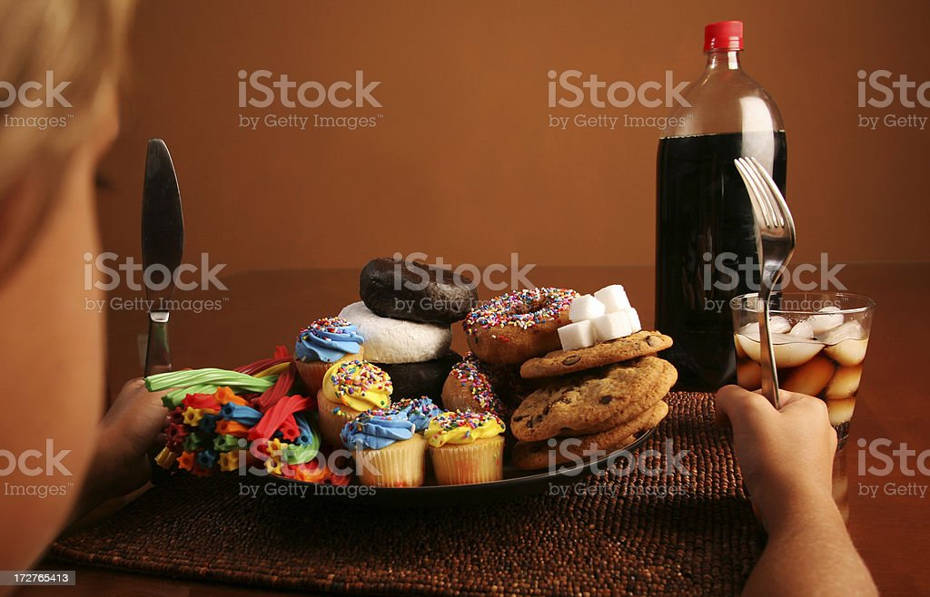 Kid with plate full of Sugar, Donuts,Candy, and Soda stock photo
