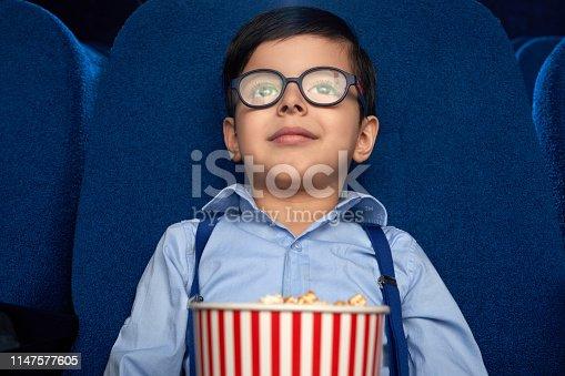 istock Kid with popcorn bucket watching cartoon in cinema. 1147577605