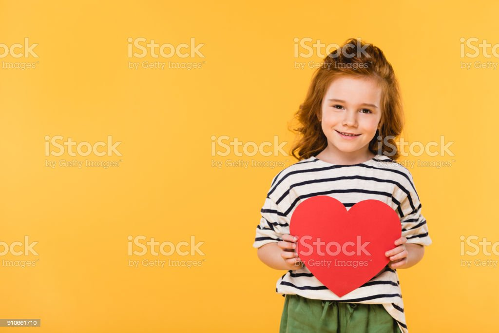 kid with red paper heart isolated on yellow, st valentines day concept - foto stock