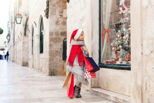 Kid with shopping bags on market street outside. Funny child is looking at store window decorated with gifts, christmas tree. Girl in red santa hat in old town. Cozy festive and New Year atmosphere. stock photo
