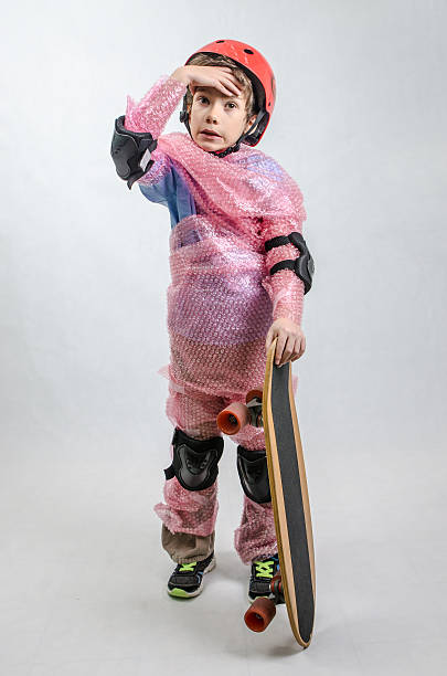Kid with skateboard wrapped in plastic bubble by overprotecting parent Kid with skateboard wrapped in plastic bubble by overprotecting parent. padding stock pictures, royalty-free photos & images