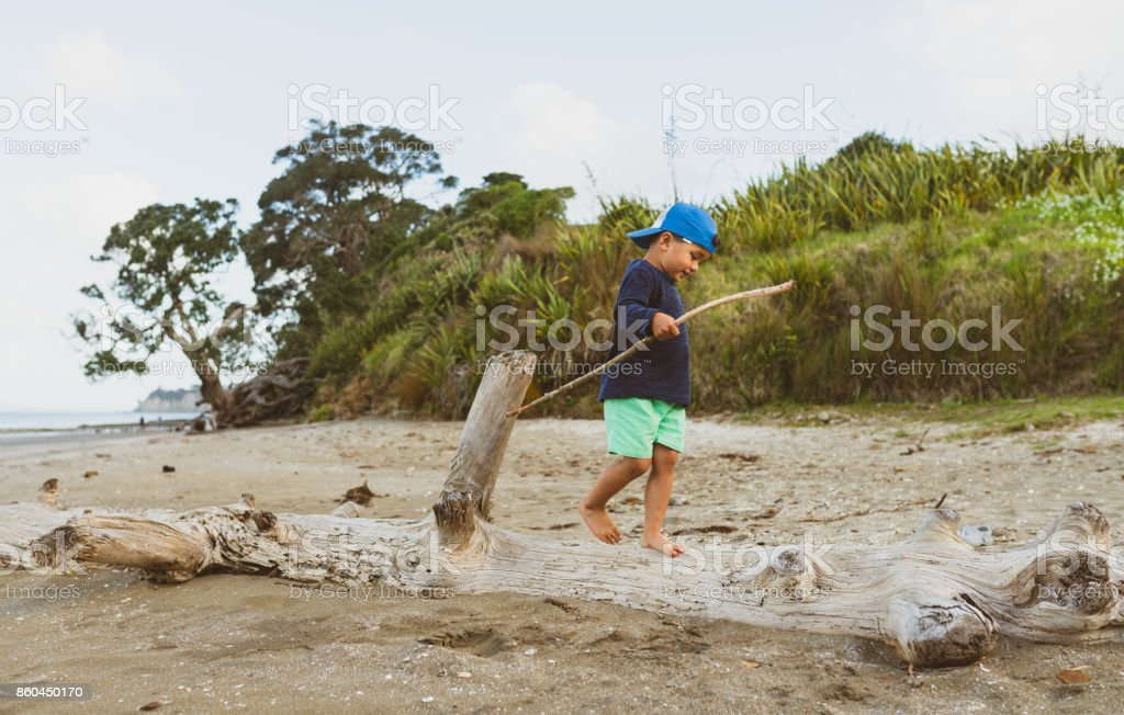 Kid with stick in hand walking on log. stock photo