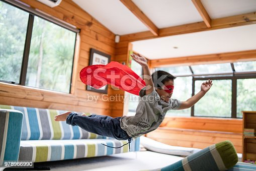 Kid with superhero mask jumping on sofa in Auckland, New Zealand.