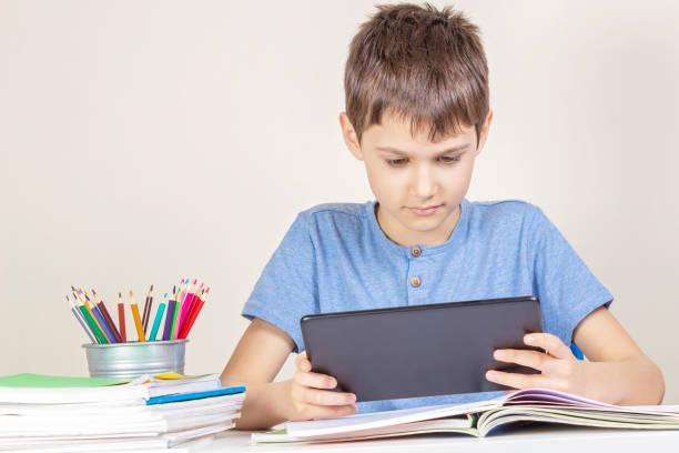 Kind mit Tablet-Computer sitzt am Tisch mit Büchern Notebooks – Foto
