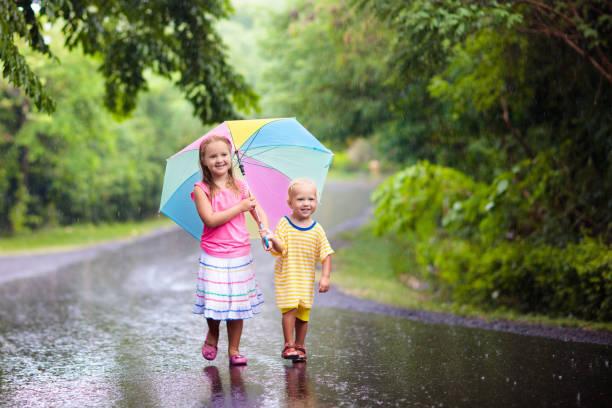 kind mit regenschirm im sommerregen spielen. - wettervorhersage deutschland stock-fotos und bilder