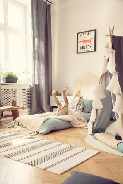 kind mit hölzernen flugzeug spielen auf blauen bett innen helle schlafzimmer mit zelt und teppich. echtes foto - fuchs kissen stock-fotos und bilder