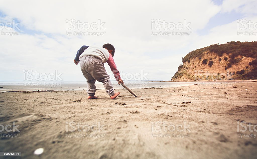 Kid writing on sand with stick. stock photo