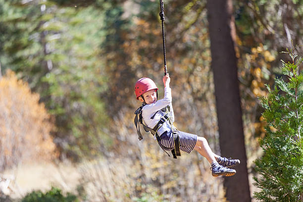 kid ziplining positive little boy ziplining at outdoor treetop adventure park being active and brave zip line stock pictures, royalty-free photos & images