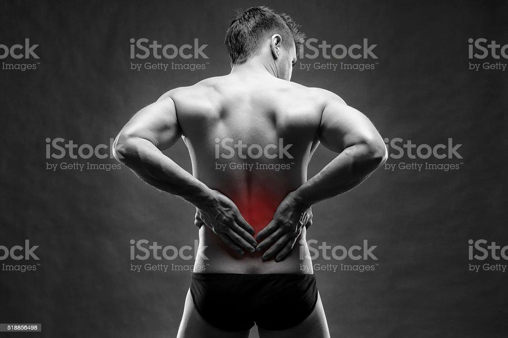 Kidney pain. Man with backache. Handsome muscular bodybuilder posing...