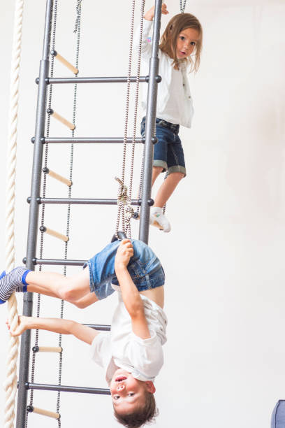 Kids Activity Concepts. Brother and Sister Playing Together During Physical Exercises on Wall Bars Indoors.Vertical Image