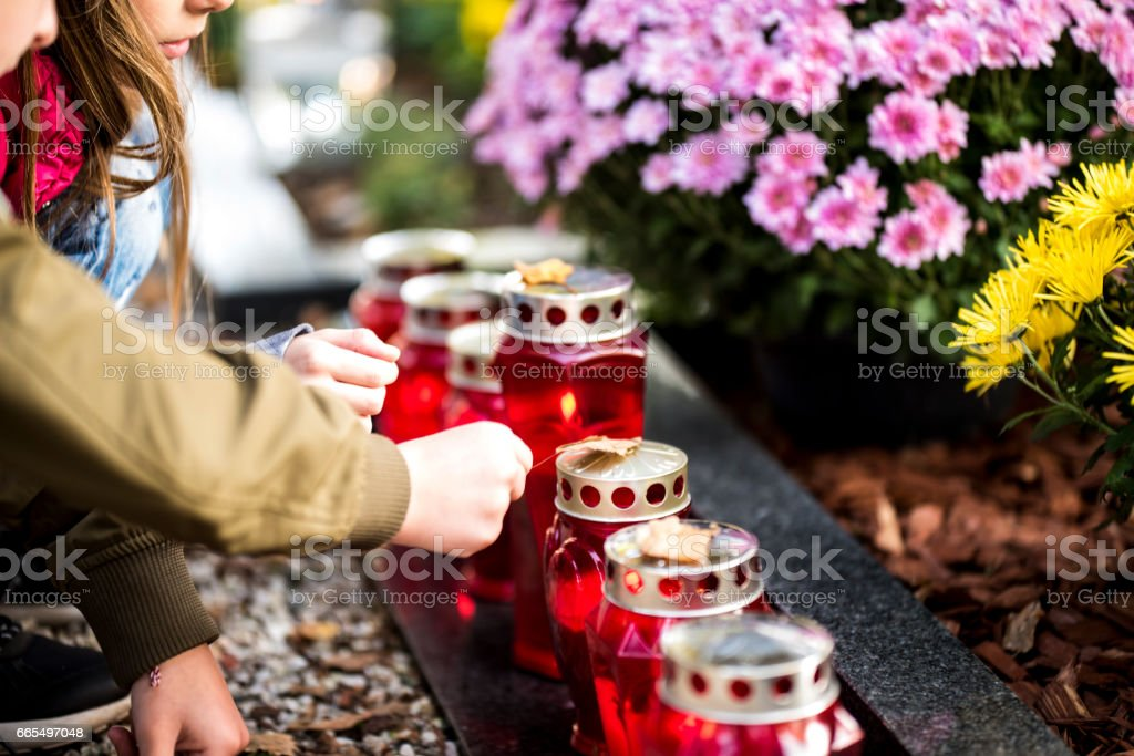 Kids and candles by the grave stock photo