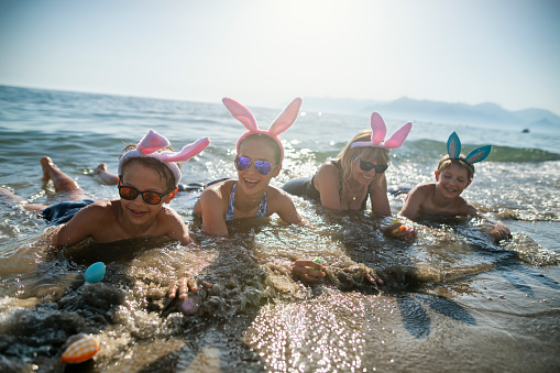 Summer Easter on beach. Kids with grandparents are lying in sea water and having fun wearing Easter bunny ears. Nikon D850