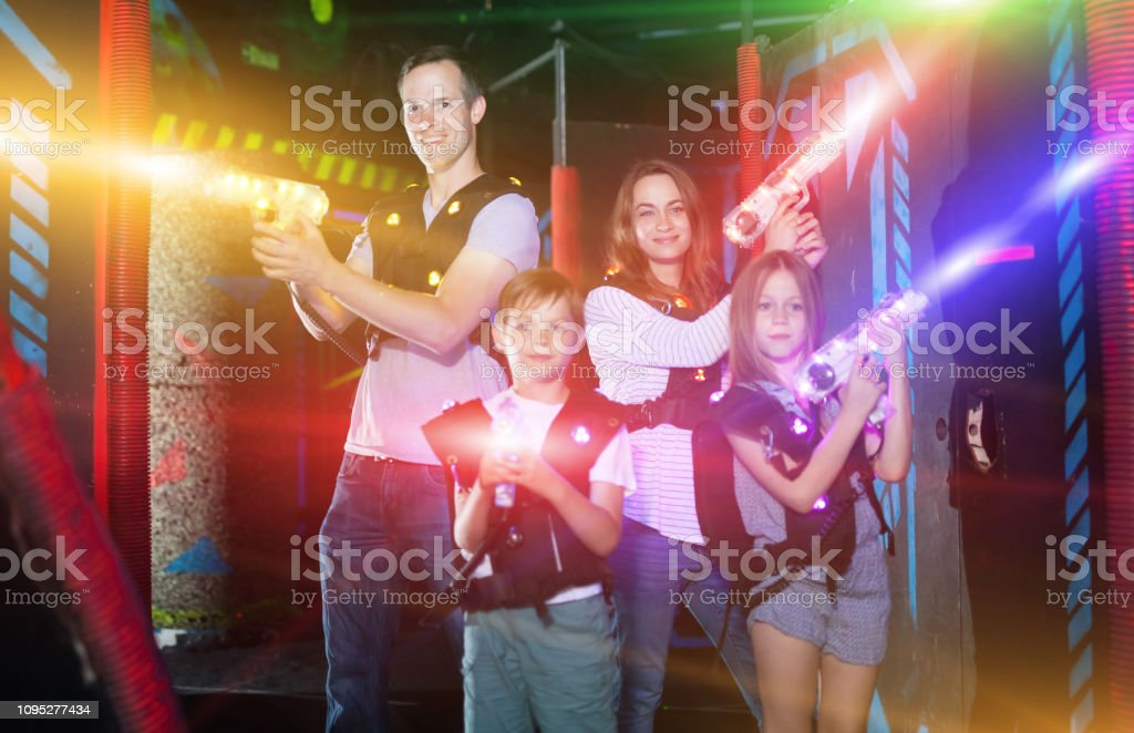 Kids And Parents In Beams During Laser Tag Game Stock Photo