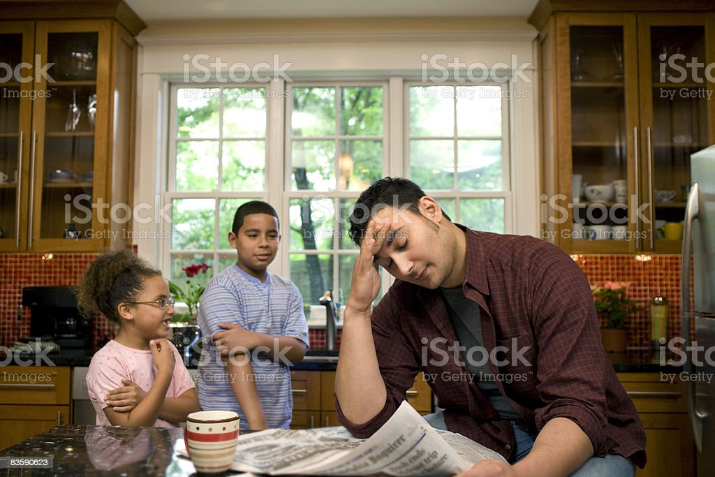 Kids annoying father at kitchen table royalty-free stock photo