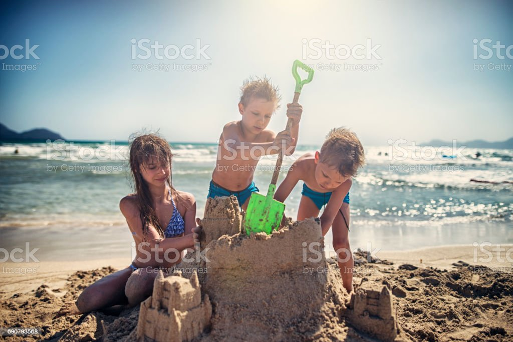Kids are building sandcastle on a beach stock photo